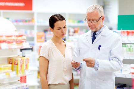 apothecary and woman with prescription at pharmacy Standard-Bild