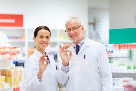 Apotheker an der Apotheke, die okayhandzeichen zeigt Standard-Bild