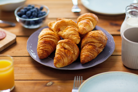 plate of croissants on wooden table at breakfast