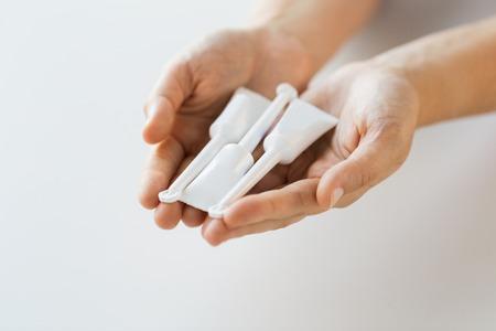hand holding tubes of micro enema Фото со стока
