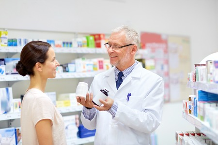 apothecary and woman with drug at pharmacy Standard-Bild
