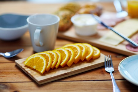 sliced orange and other food on wooden table Standard-Bild