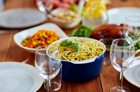pasta with basil in bowl and other food on table Standard-Bild