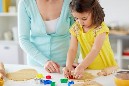 happy mother and daughter making cookies at home Standard-Bild