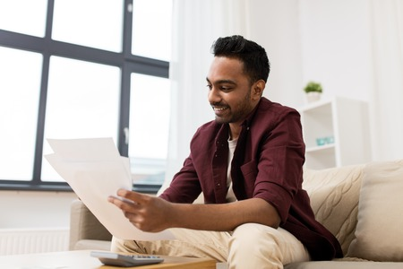 man with papers and calculator at home Stock Photo