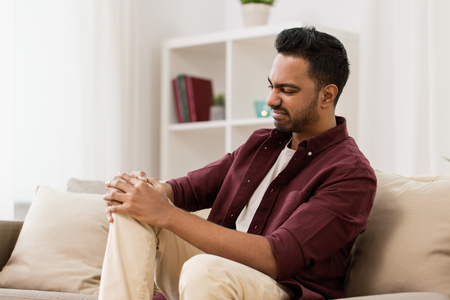 unhappy man suffering from pain in leg at home