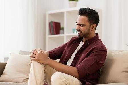 homem infeliz, sofrendo de dor na perna em casa