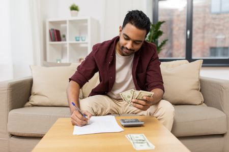 man with money and calculator filling papers
