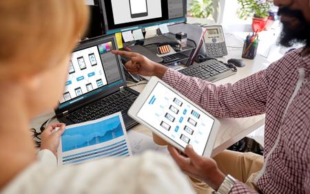 Mensen, technologie en web design concept - ontwerpers team met laptop, grafiek en tablet pc-computer op kantoor Stockfoto - 91911118