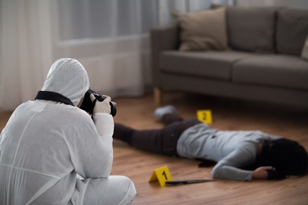 investigation, forensic examination and people concept - criminalist with camera photographing dead female victim body at crime scene (staged photo) Stockfoto