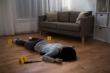 moord, doden en mensen concept - lichaam van de dode vrouw en mes in bloed liggend op de vloer op plaats delict (geënsceneerde foto)