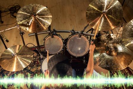 male musician playing drum kit at studio