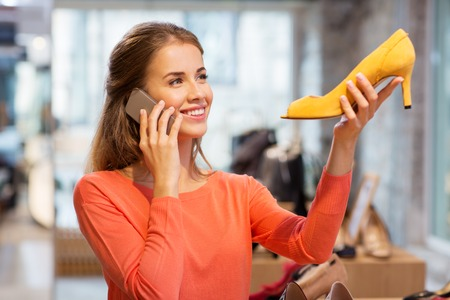 young woman calling on smartphone at shoe store
