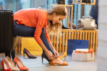 young woman trying sandals at shoe store Stock Photo