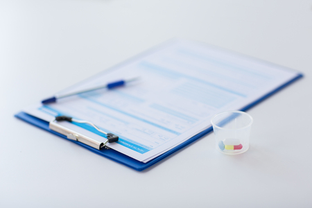 clipboard with report and drugs in medical cup