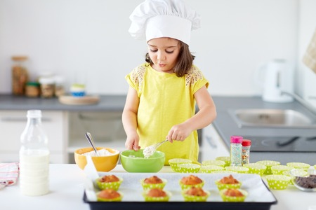 little girl in chefs toque baking muffins at home Reklamní fotografie - 92103548