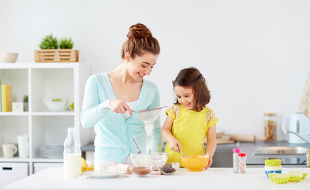 happy mother and daughter baking at home