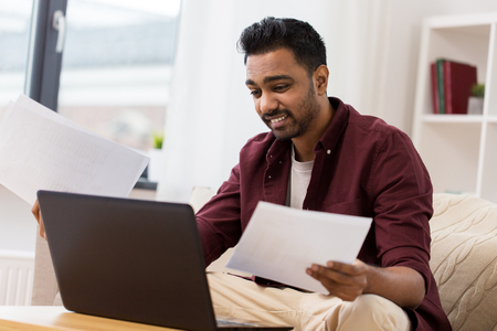 confused man with laptop and papers at home
