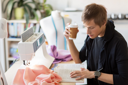 fashion designer with coffee and book at studio Stock Photo