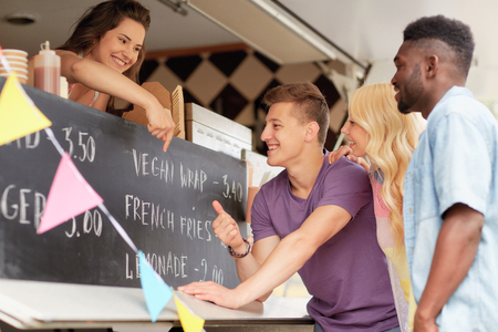 happy customers or friends at food truck Stock Photo