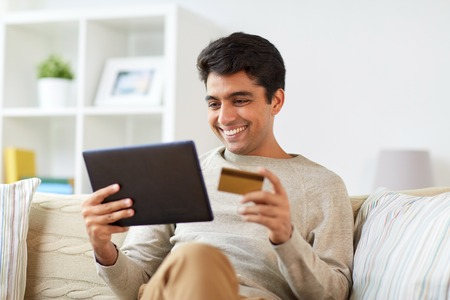 smiling man with tablet pc and credit card at home