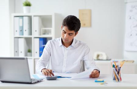 zakenman met papieren en rekenmachine op kantoor Stockfoto