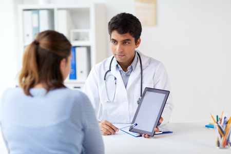 doctor showing tablet pc to patient at clinic