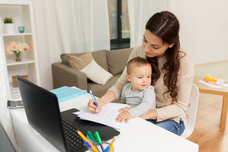 happy mother with baby and papers working at home Standard-Bild