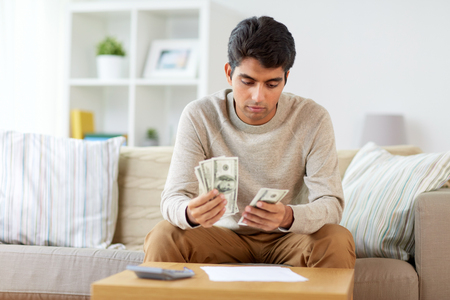man with calculator counting money at home