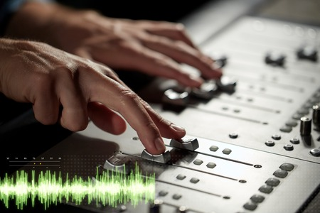 hands on mixing console at sound recording studio