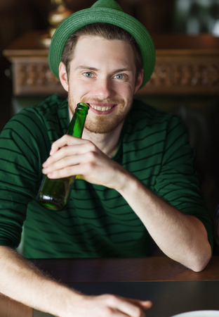 man drinking beer from green bottle at bar or pub