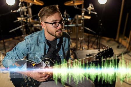 musician playing guitar at studio rehearsal
