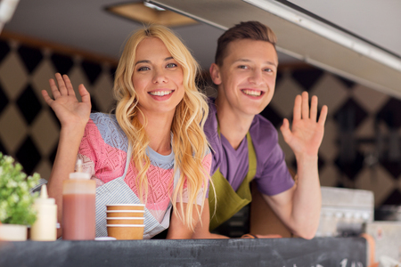 happy young sellers waving hands at food truck