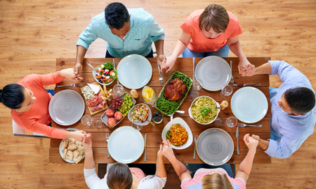 group of people at table praying before meal Imagens