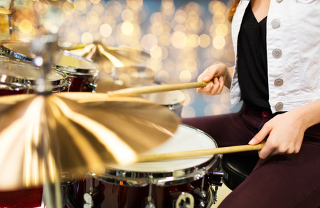 people, musical instruments and entertainment concept - close up of female musician playing drum kit over lights Фото со стока - 92983767