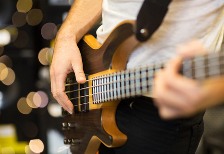 musical instruments, entertainment and people concept - close up of male musician playing guitar at music studio over lights background