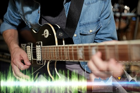 music, people, musical instruments and entertainment concept - close up of male guitarist playing electric guitar at studio rehearsal 写真素材