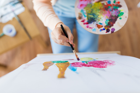 art, creativity and people concept - close up of artist with palette and paint brush painting still life on paper at studio Banque d'images
