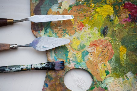fine art, creativity and artistic tools concept - close up of palette knives or painting spatulas and paintbrush from top