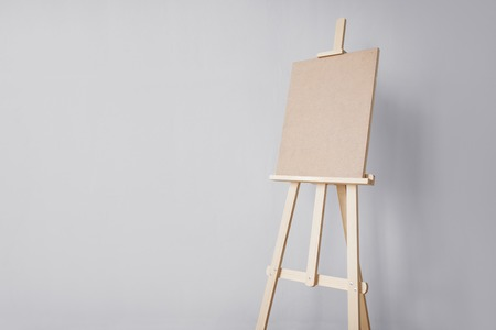fine art, creativity and artistic tools concept - wooden easel at studio