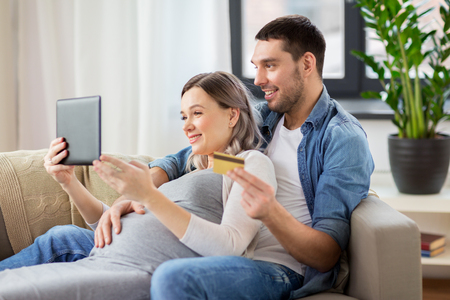 online shopping, pregnancy and technology concept - happy man and his pregnant wife with tablet pc computer and credit card at home Archivio Fotografico