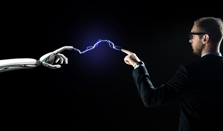 business, future technology and artificial intelligence concept - businessman and robot hand connected by lightning over black background