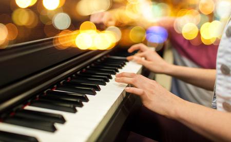 Música, instrumentos musicais e conceito de pessoas - close-up de mãos de mulher tocando piano sobre fundo de luzes Foto de archivo - 93050704