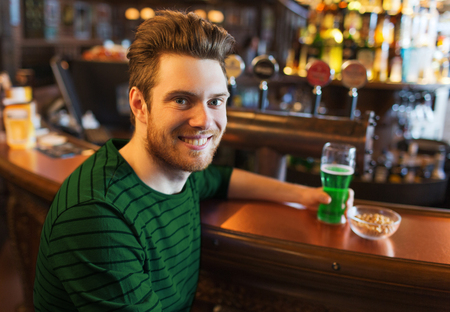 people, leisure and st patricks day concept - happy young man drinking green beer at bar or pub Stock Photo