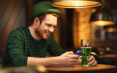 st patricks day, people and technology concept - happy man with smartphone drinking green beer and reading message at bar or pub