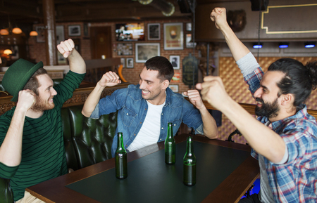 people, friendship and st patricks day concept - happy male friends drinking bottled beer and and celebrating at bar or pub Stockfoto