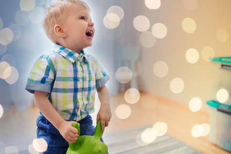 childhood, toys and people concept - happy little baby boy playing with ride-on toy horse at home Stok Fotoğraf