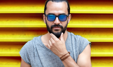 fashion, style, eyewear and people concept - close up of man in sunglasses touching beard over ribbed yellow wall background