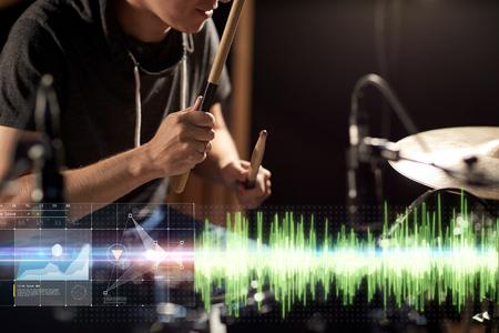 muziek, mensen, muziekinstrumenten en entertainment concept - mannelijke muzikant met drumsticks drumstel spelen op concert of studio