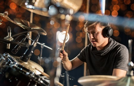 music, people, musical instruments and entertainment concept - male musician in headphones with drumsticks playing drum kit at concert or studio over holidays lights background